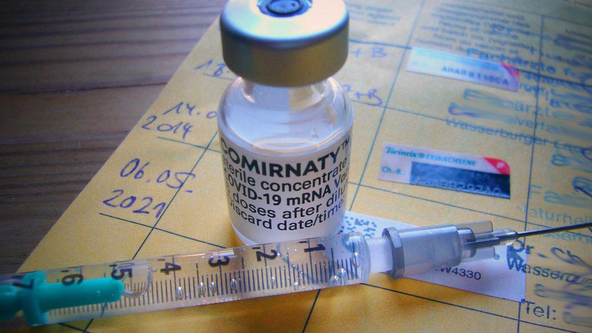 Das Vakzin Comirnaty des Herstellers BioNTech Pfizer und eine Impfspritze auf einem Impfbuch.