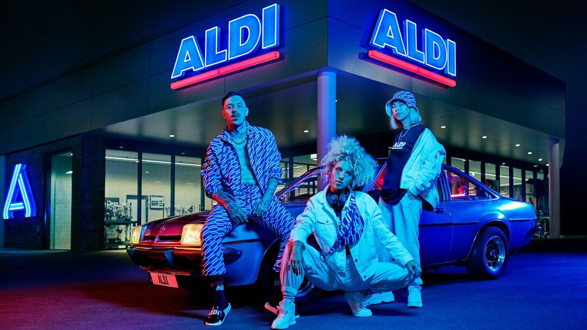 Zwei Frauen und ein Mann posieren in den neuen Aldi-Klamotten vor einer Filiale des Discounters.