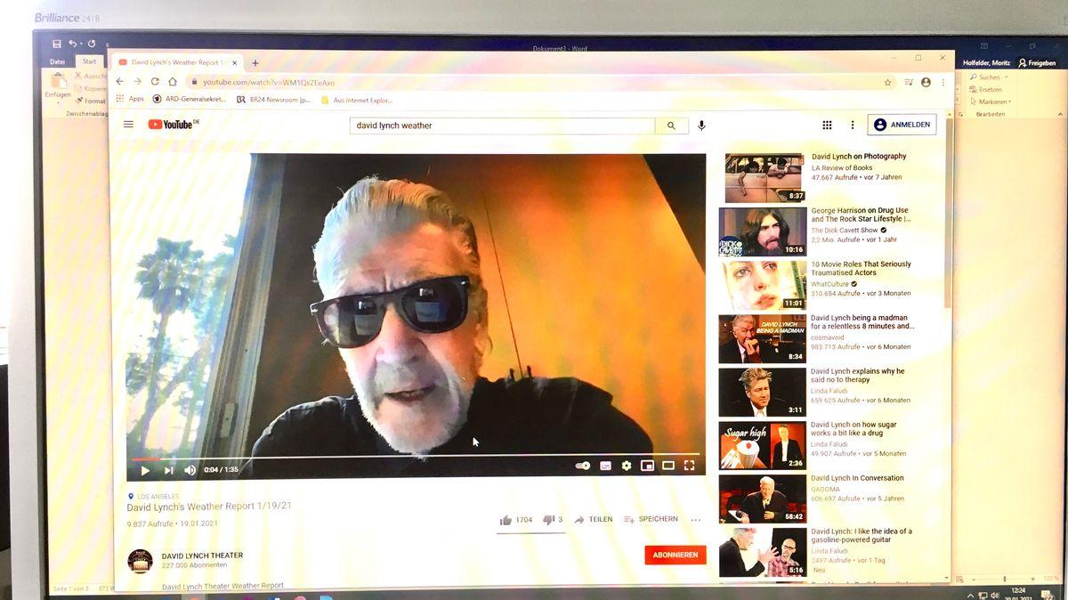 Man sieht einen Computerbildschirm, auf dem der Filmemacher David Lynch mit dunkler Sonnenbrille und zurückgekämmten weißen Haaren erscheint.
