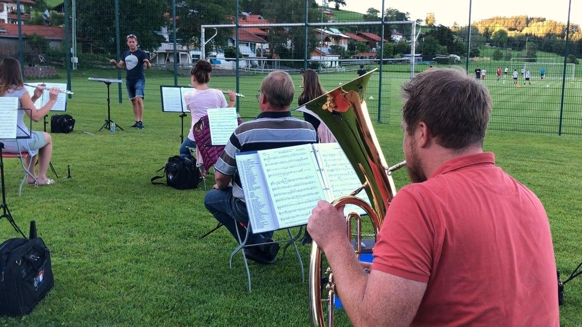 Probe der Musikkapelle Niedersonthofen auf dem Sportplatz, nebenan trainieren die Fußballer.