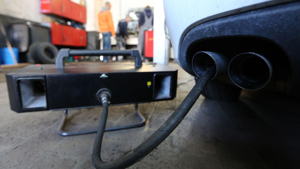 Der Messschlauch eines Geräts zur Abgasuntersuchung für Dieselmotoren steckt im Auspuffrohr eines Audi A4 TDI in einer Werkstatt.
