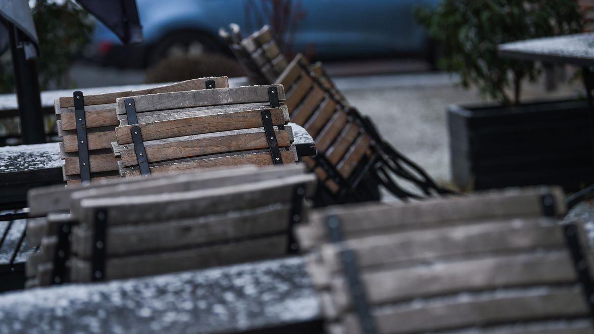 An einem Restaurant stehen zusammengeklappte Stühle.