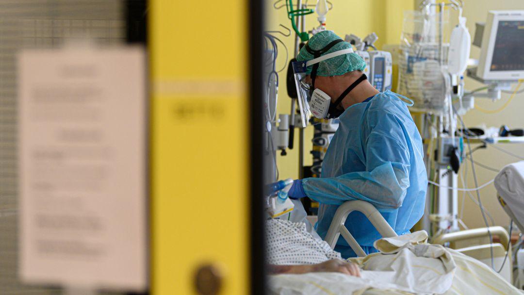 Ein Intensivpfleger versorgt Corona-Patienten auf einer Intensivstation.