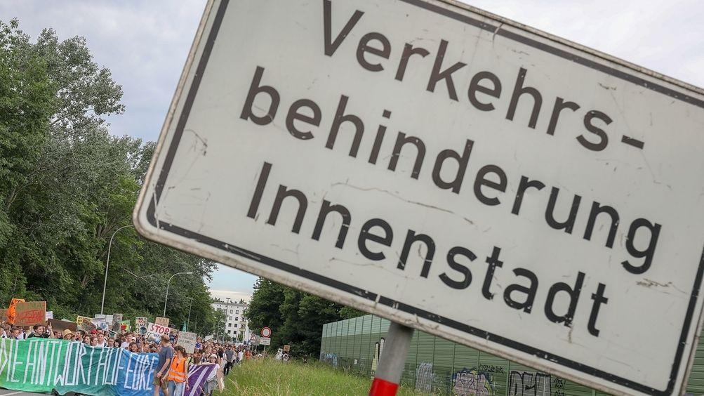 """""""Verkehrsbehinderung Innenstadt"""" steht auf einem Schild vor einer Fridays for Future-Demo"""