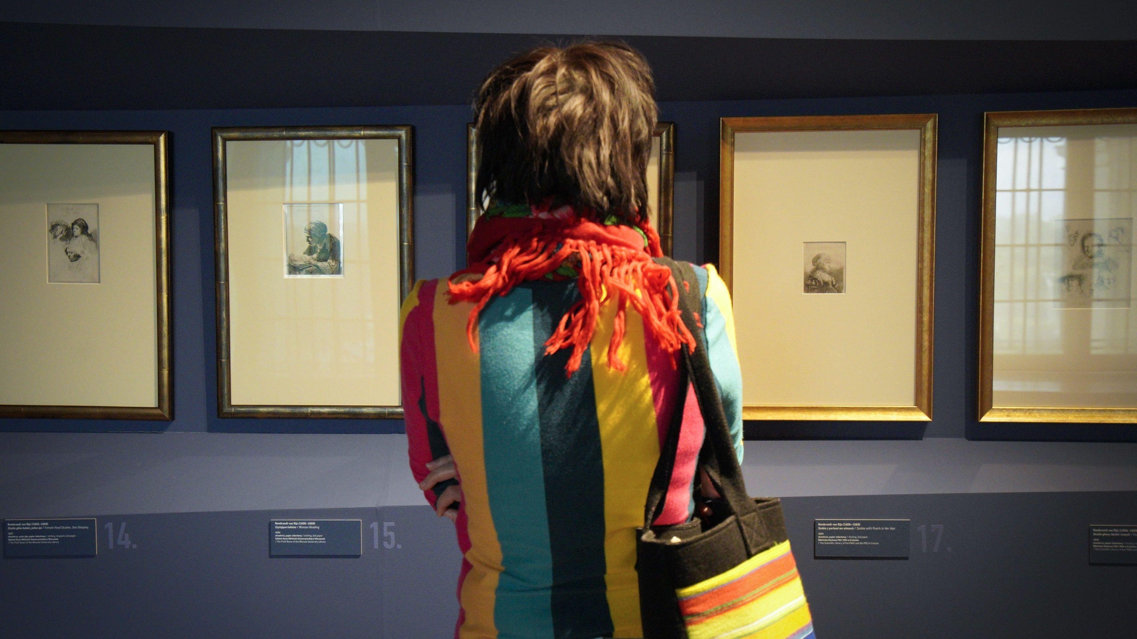 Eine Frau steht vor Gemälden in einem Museum.