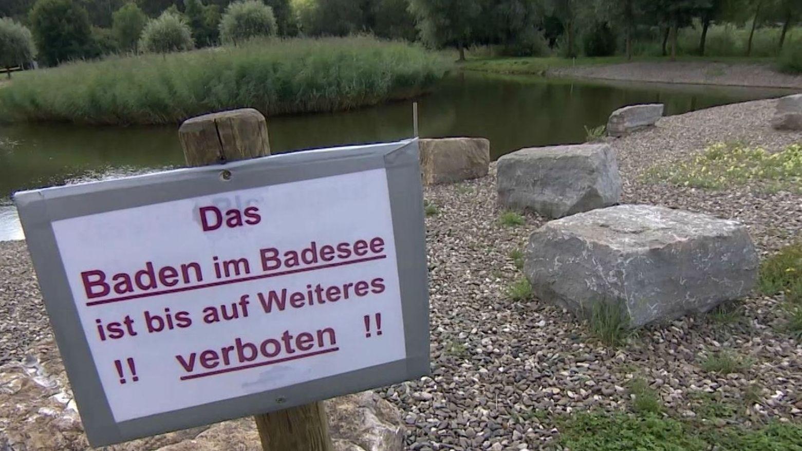 """Ein Schild am Ufer eines Badeteichs mit der Aufschrift """"Das Baden im Badesee ist bis auf Weiteres verboten""""."""