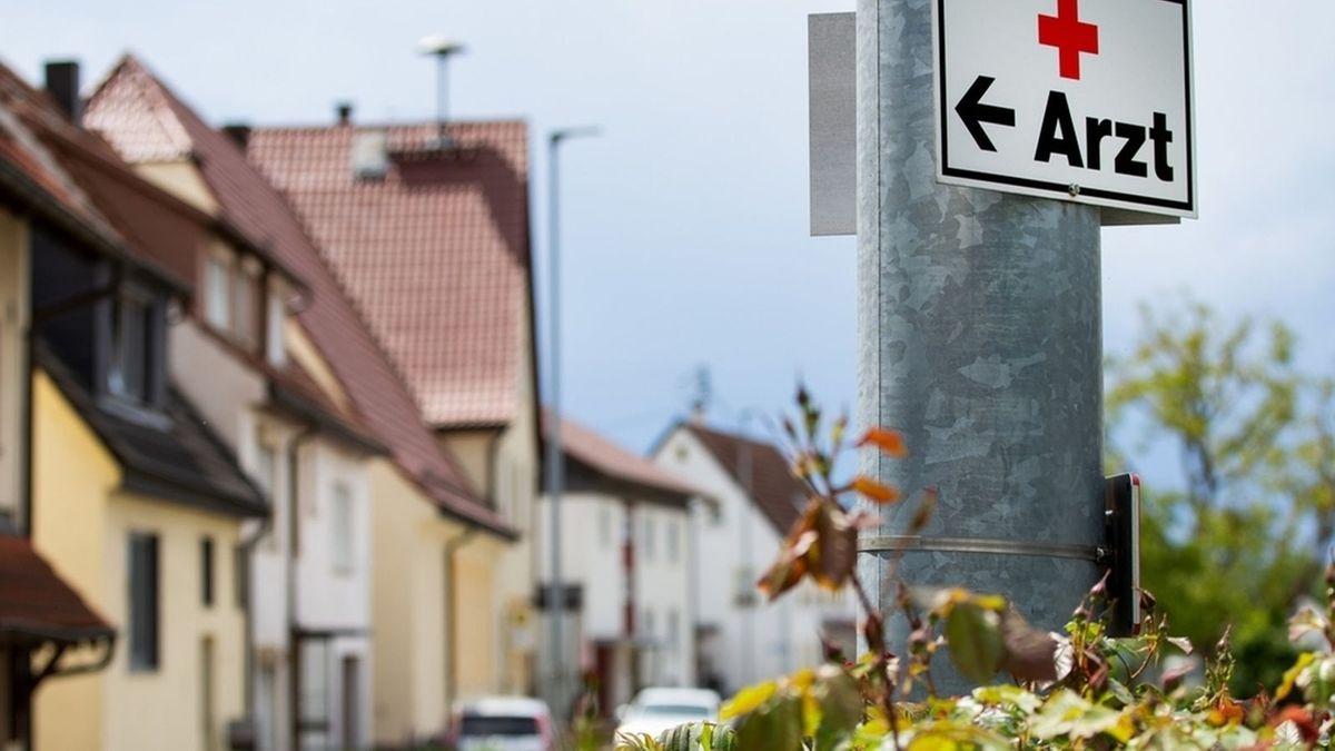 """Ein weißes Hinweisschild mit einem roten Kreuz, dem Wort """"Arzt"""" und einem schwarzen Richtungspfeil ist an einem Masten befestigt, dahinter eine Häuserzeile."""