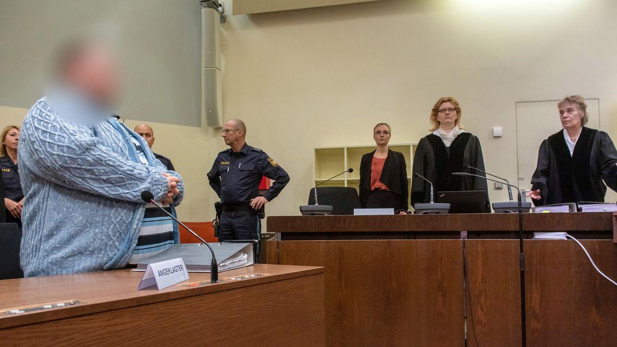 Links vorne steht der angeklagte Hilfspfleger im Gerichtssaal des Landgerichts München I. Im Hintergrund die Richterbank, ganz rechts Elisabeth Ehrl, Vorsitzende der ersten Strafkammer am Landgericht München I.
