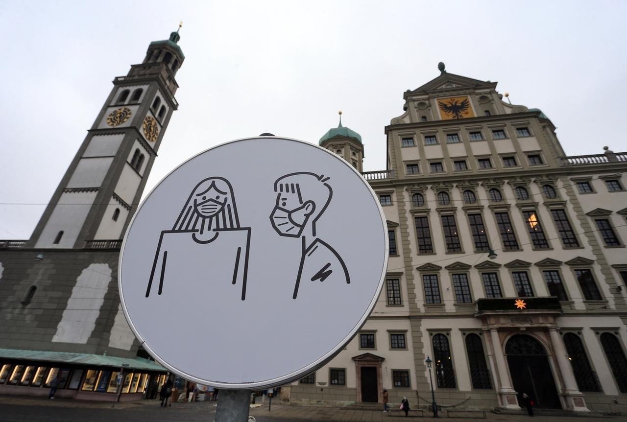 ARCHIV - 05.01.2021, Bayern, Augsburg: Ein Schild weist auf dem Rathausplatz auf Maskenpflicht hin. (zu dpa «Maskenpflicht bei Sitzungen? Gemeinderäte dürfen selbst entscheiden») Foto: Karl-Josef Hildenbrand/dpa +++ dpa-Bildfunk +++
