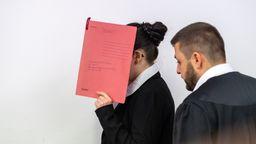Die Angeklagte, die sich der Terrormiliz Islamischer Staat (IS) im Irak angeschlossen haben soll, hält sich beim Betreten des Gerichtssaals einen roten Aktendeckel vors Gesicht. Recht steht ihr Anwalt Ali Aydin. (Archivbild)   Bild:pa/dpa/Peter Kneffel