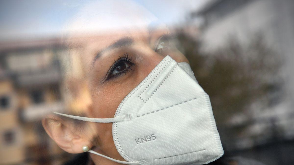 Junge Frau mit FFP2-Maske blickt sorgenvoll aus einem Fenster