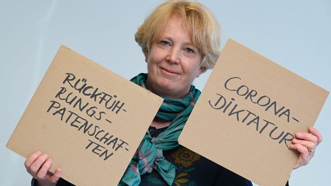 Prof. Dr. Nina Janich hält zwei Pappschilder in die Kamera, auf denen die Unwörter des Jahres 2020 stehen