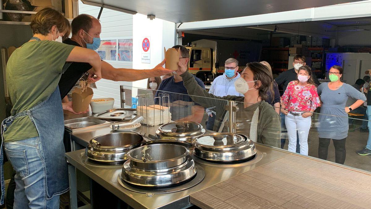 Helferessen beim BRK in Bayreuth: Menschen stehen bei der Essensausgabe in einer Schlange.