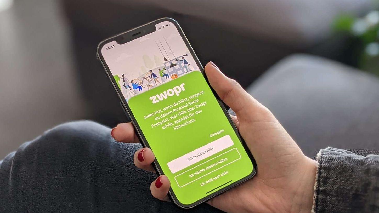 Hand hält Smartphone, das die Zwopr-App anzeigt.