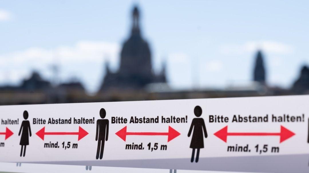 """Sachsen, Dresden: Ein Absperrband mit der Aufschrift """"Bitte Abstand halten"""" hängt am Zugang zu einer Terrasse vor einem Restaurant."""