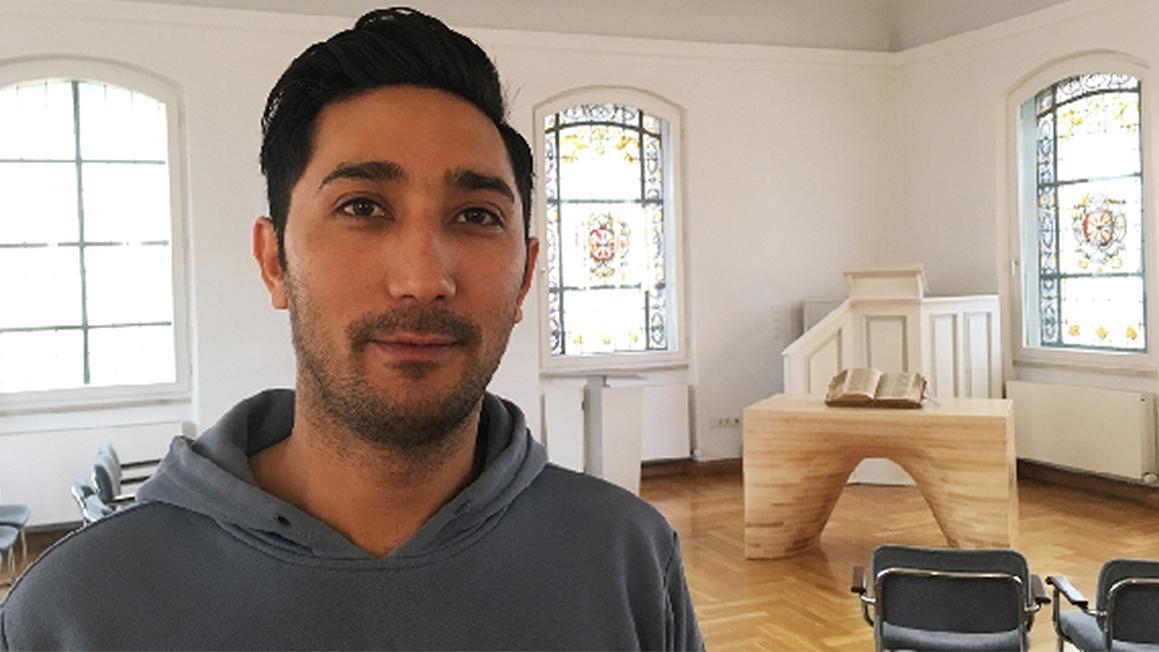 Danial M. aus Afghanistan im Kirchenasyl: Er steht in einem Raum der evangelisch-reformierten Kirche in Bayreuth.