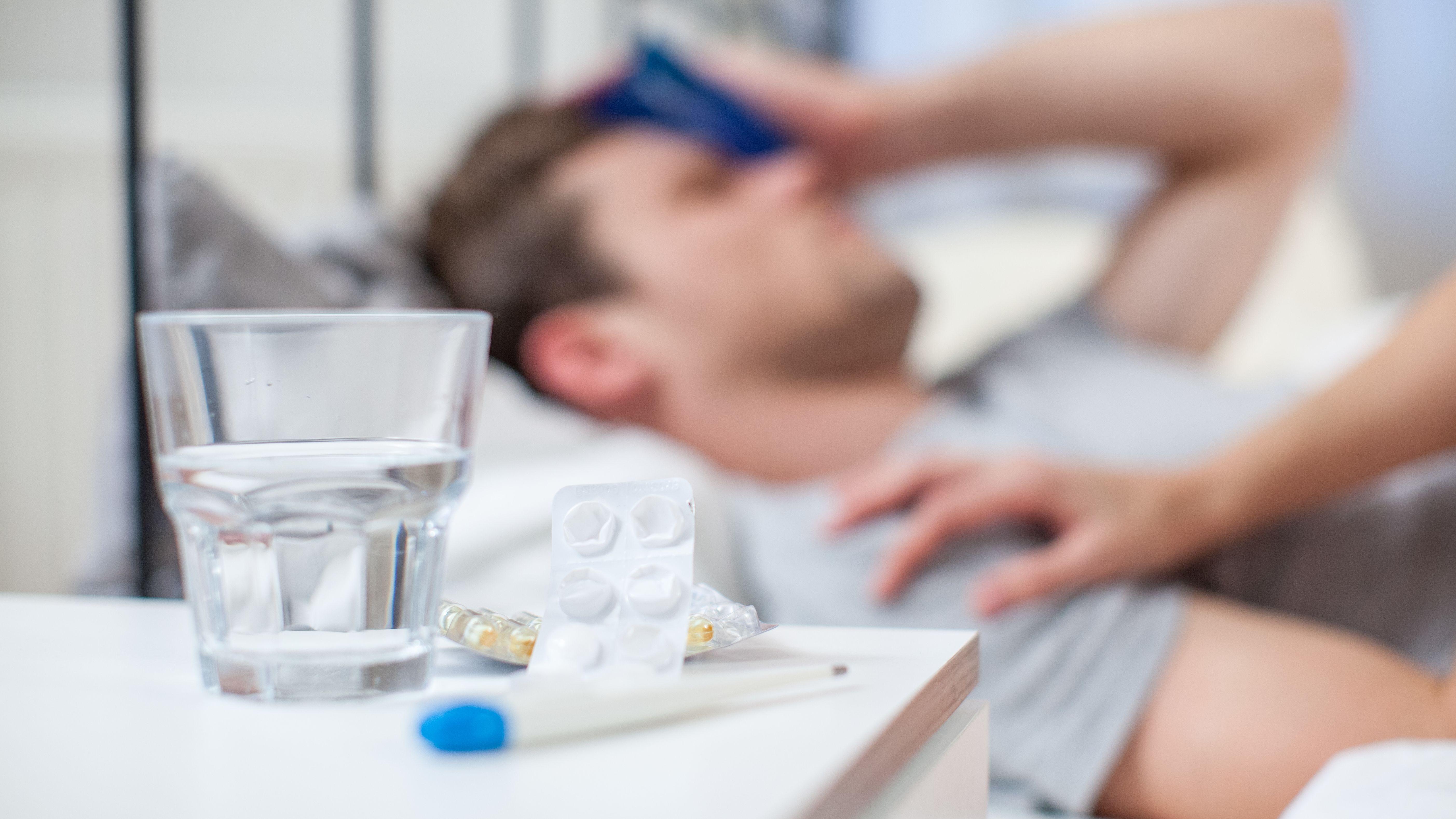 Ein Mann liegt krank im Bett. Am Nachtisch sind Tabletten, ein Fieberthermometer und ein Glas Wasser zu sehen.