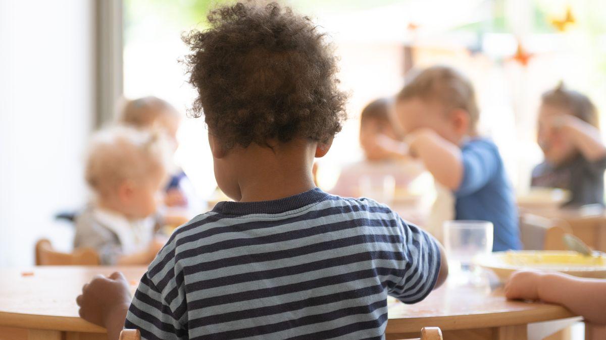 Kinde sitzen beim Essen in einer Kindertagesstätte zusammen.