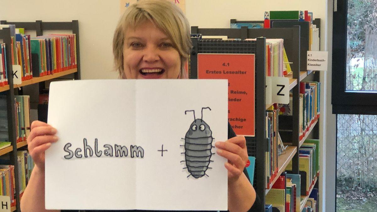 Autorin hält ein Schild hoch auf dem Schlamm steht. Dahinter kommt ein Pluszeichen und eine gezeichnete Assel