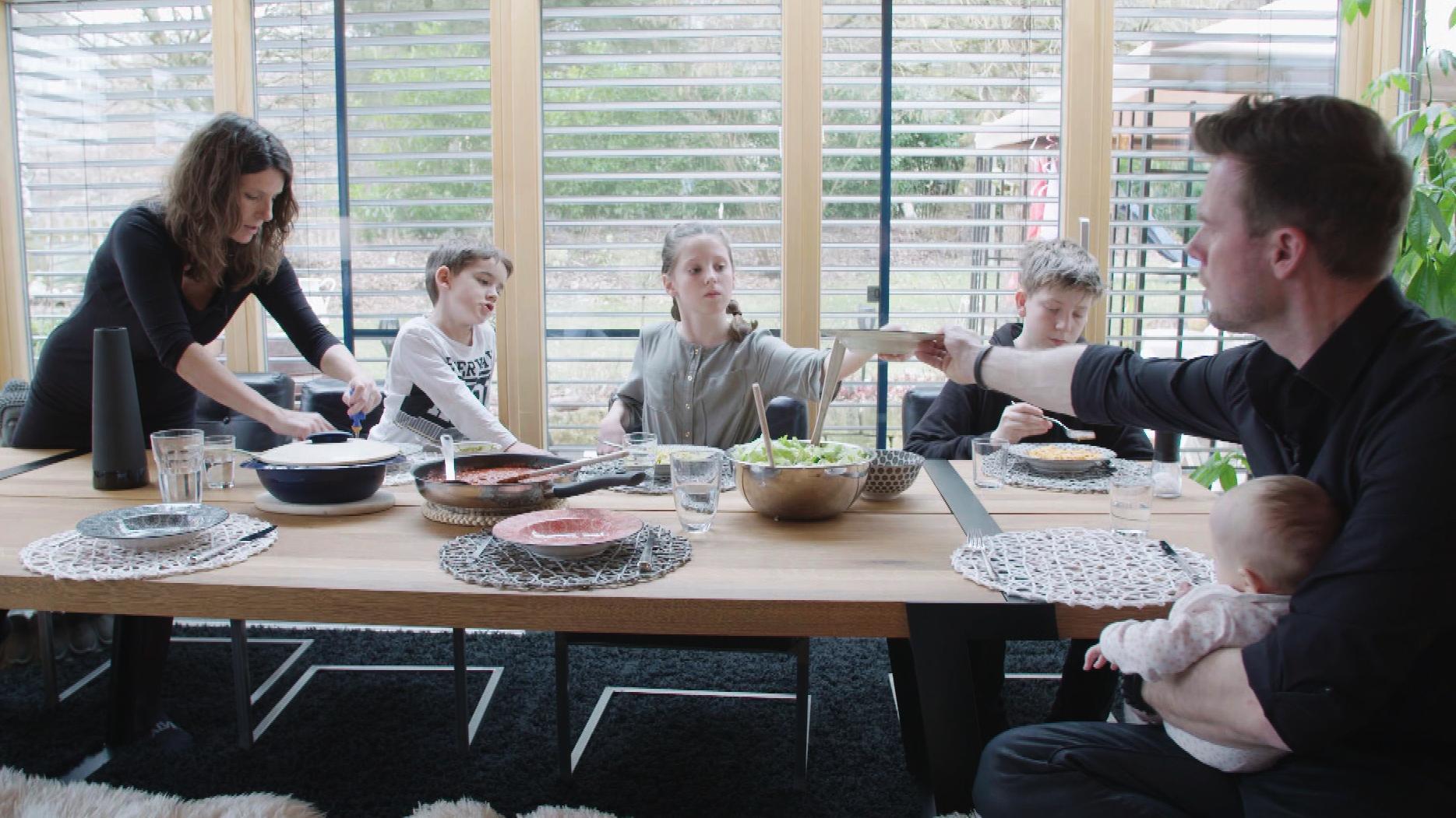 Vater, Mutter und vier Kinder am Esstisch