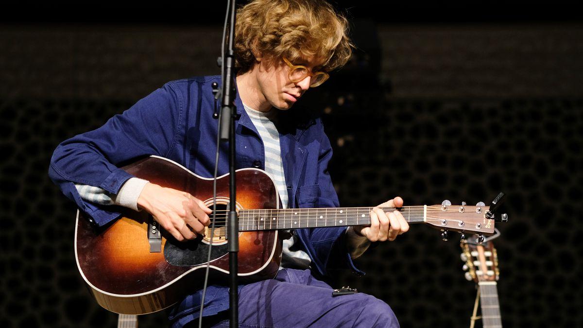 Musiker Erlend Oye spielt sitzend Gitarre.