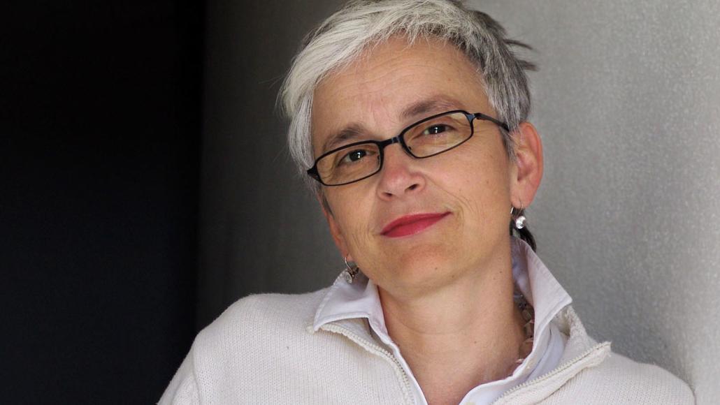 Barbara Mundel sitzt vor einer grauen Wand und lächelt in die Kamera