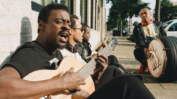 Die brasilianischen Musiker Seu Jorge & Rogê sitzen mit Gitarre und improvisierter Tromme auf der STraße