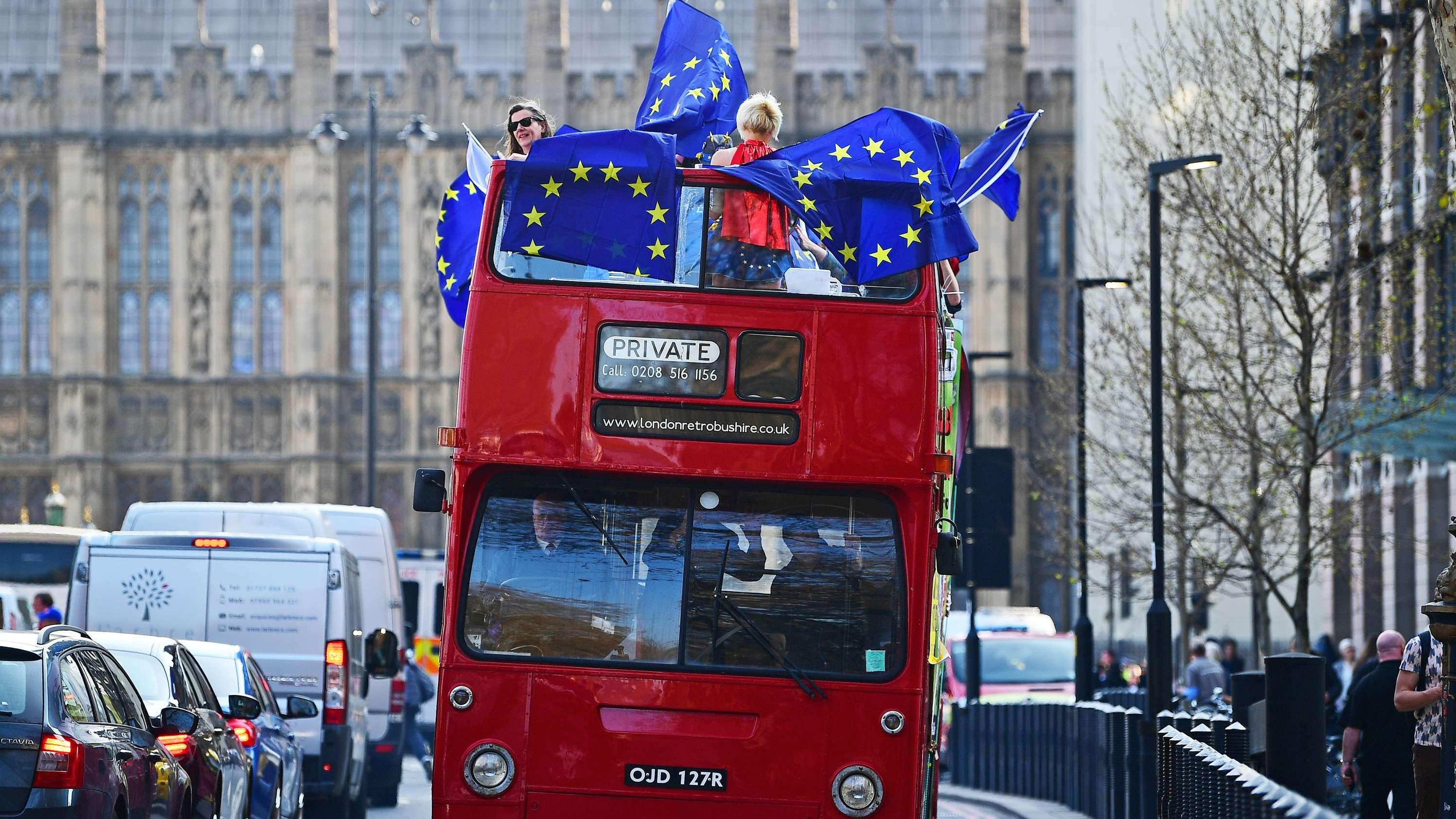 Brexit-Gegner stehen mit EU-Fahnen auf einem Bus vor dem Parlament.