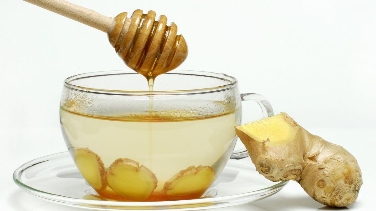 Ingwertee mit Honig und eine ingwerwurzel