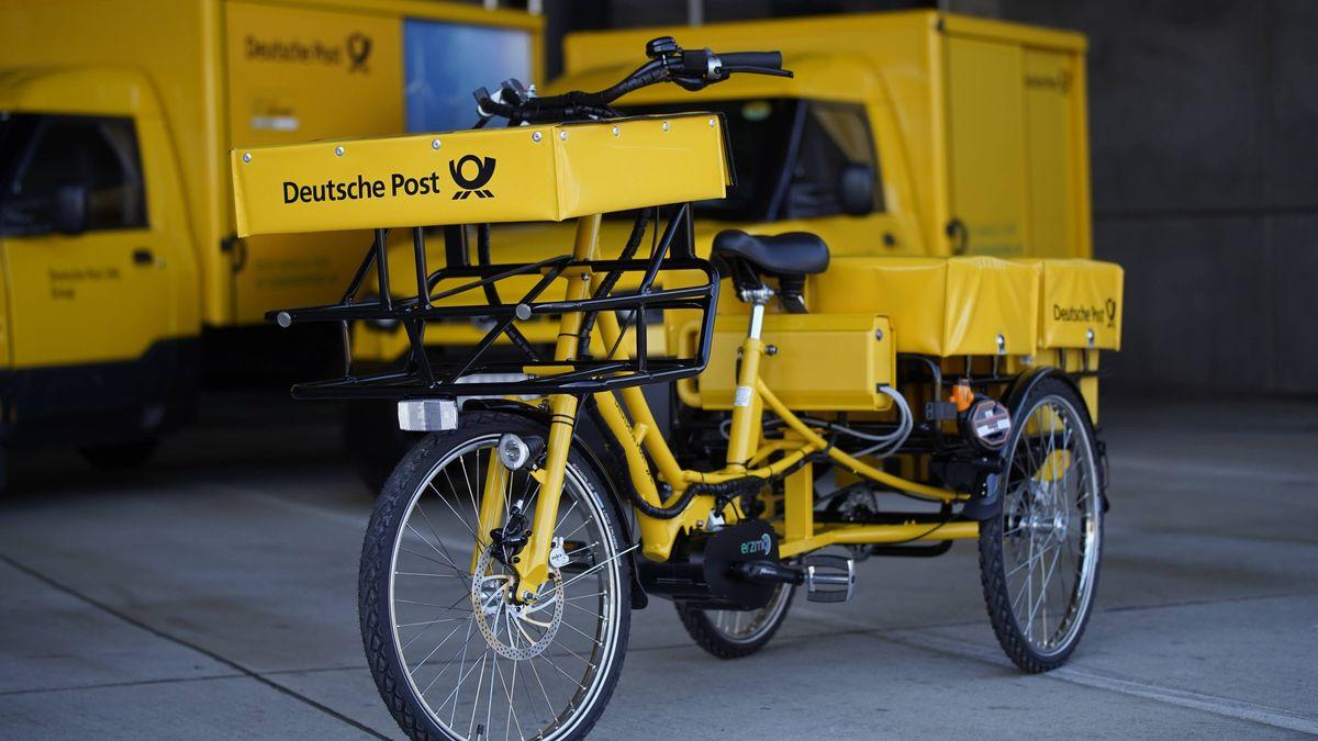 Ein Fahrrad und Zustellfahrzeuge der Deutschen Post