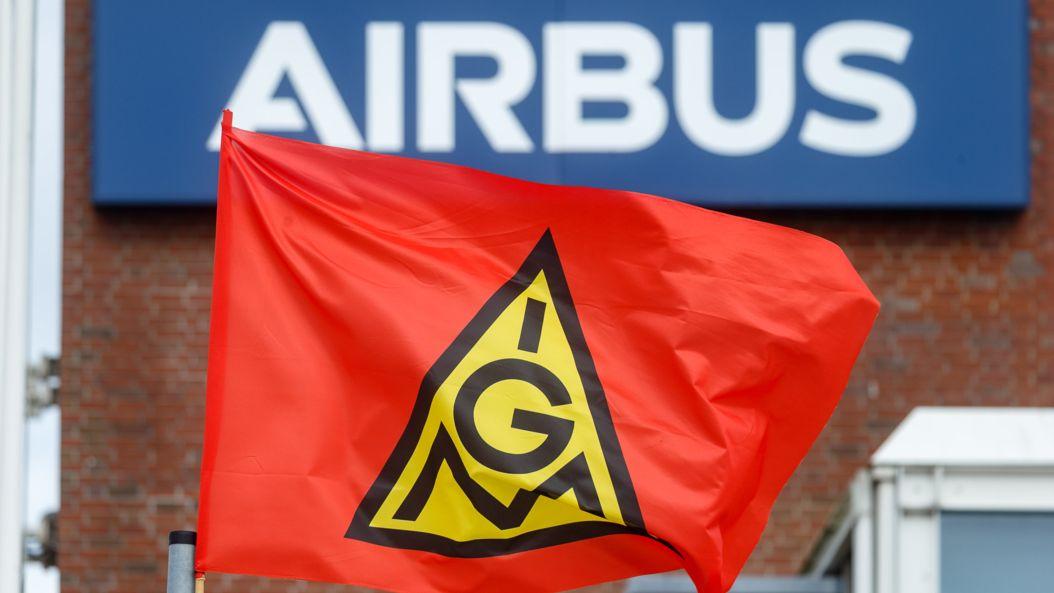 """17.09.2021, Hamburg: Eine Fahne der IG-Metall weht bei einem Warnstreik vor dem Schriftzug """"Airbus"""" an dem Werk in Hamburg-Finkenwerder."""