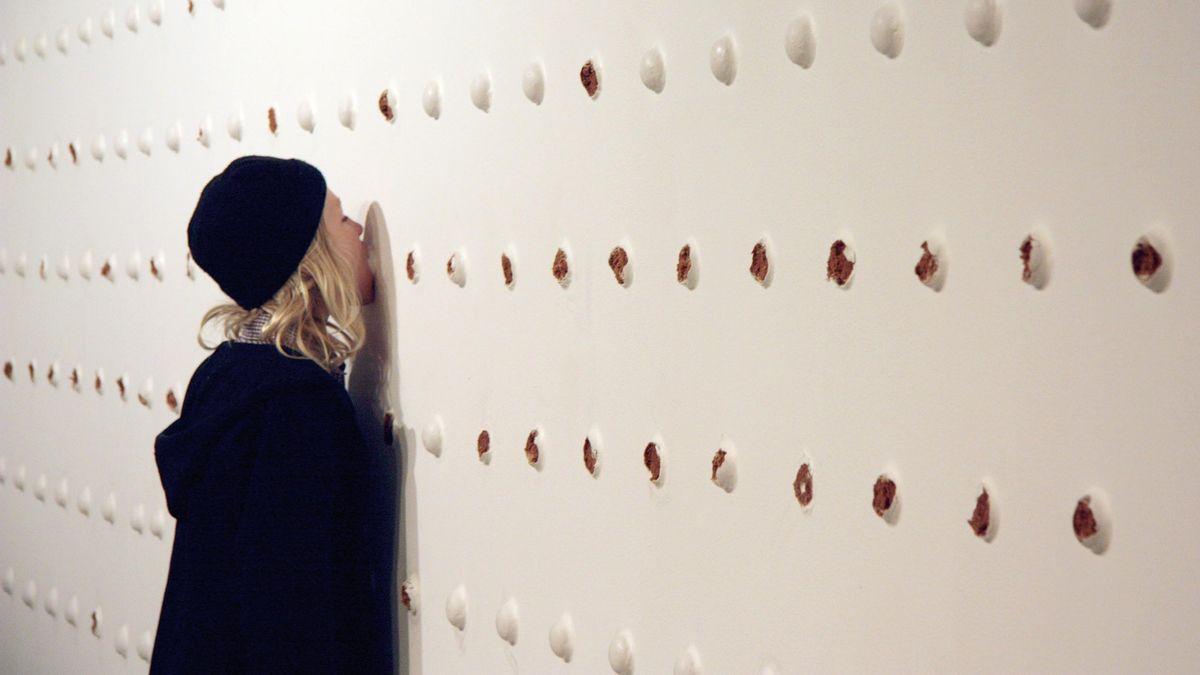 Eine Frau steht leckend vor einer 22 Meter langen Wand mit Reihen von weißen Knöpfen, die sich beim näheren Hinsehen/Schmecken als Pfefferkuchen herausstellen.