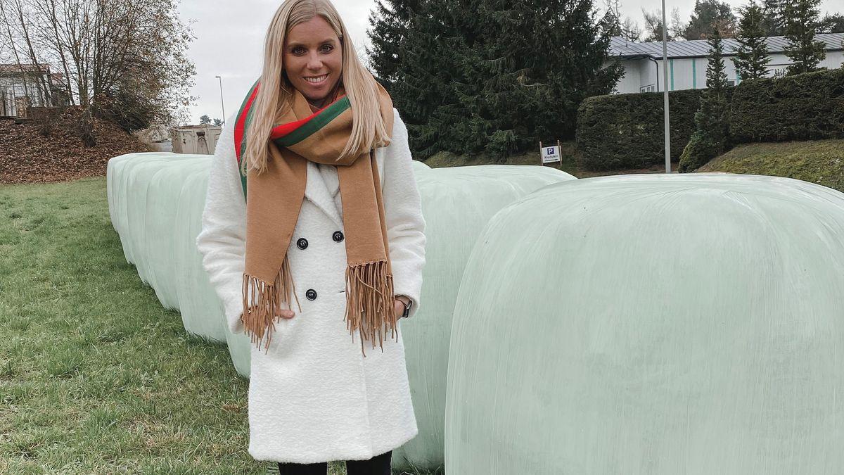 Isabell Kleiber im weißen Mantel und braunem Schal steht neben Silageballen, die in weißen Kunststofffolien verpackt sind.