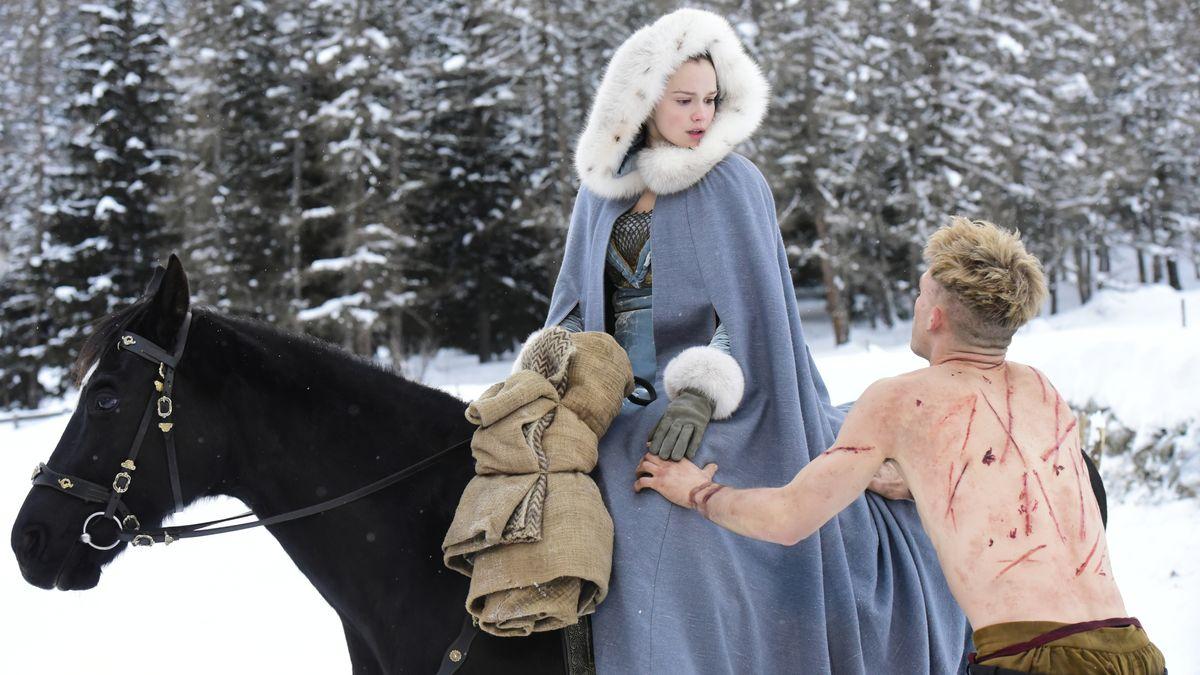 Mann mit nacktem, vernarbten Oberkörper wendet sich in kalter Winterlandschaft einer jungen Frau auf einem Pferd zu, die ein Gewand mit Fellkapuze trägt.
