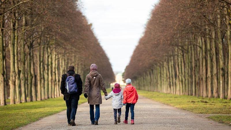 Eine Familie geht in einem Park spazieren.