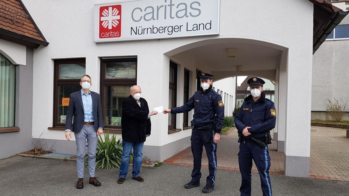 Zwei Polizisten in Uniform übergeben einen Spendenscheck an zwei Vertreter der Caritas vor der Geschäftsstelle.