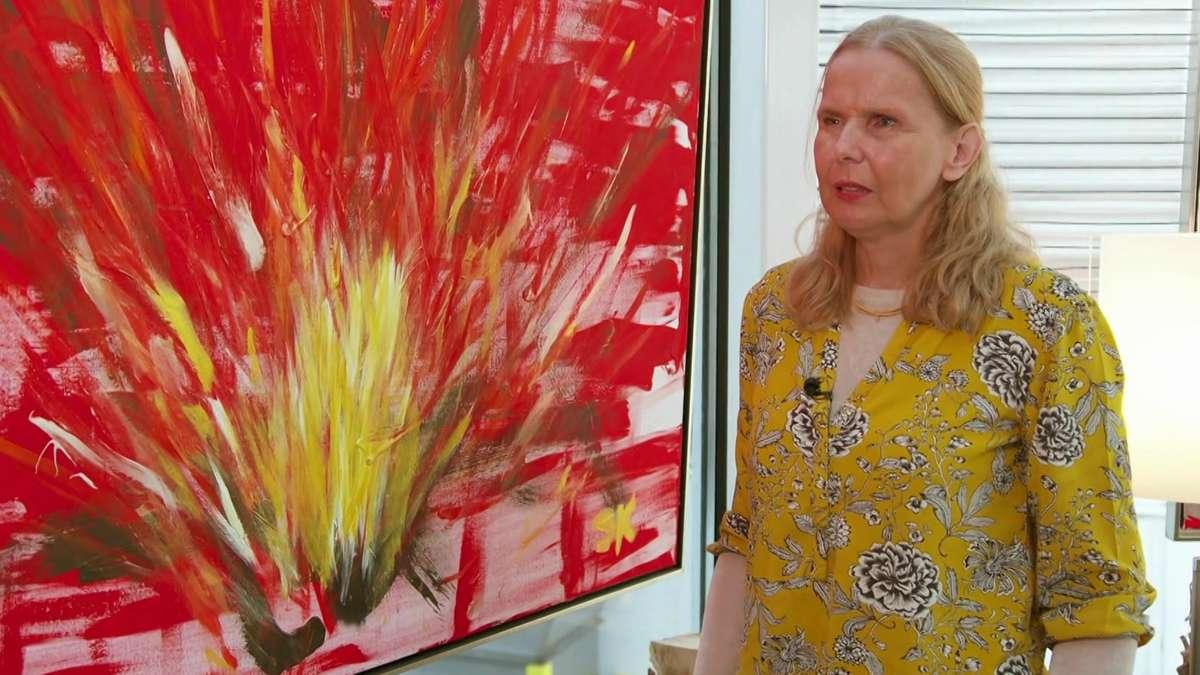 Die Künstlerin steht neben einem Bild, auf dem ein Lagerfeuer zu sehen ist, Flammen lodern nach oben.