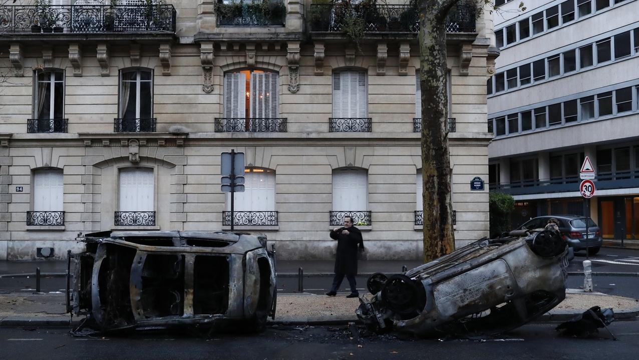 Ein Mann macht am Tag nach den Ausschreitungen in der Nähe des Arc de Triomphe in Paris ein Foto von ausgebrannten Autos.