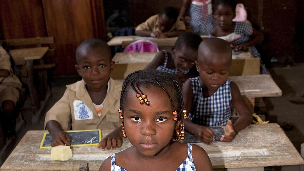 Kinder sitzen an Tischen in einer Schule in Afrika (Symbolbild)