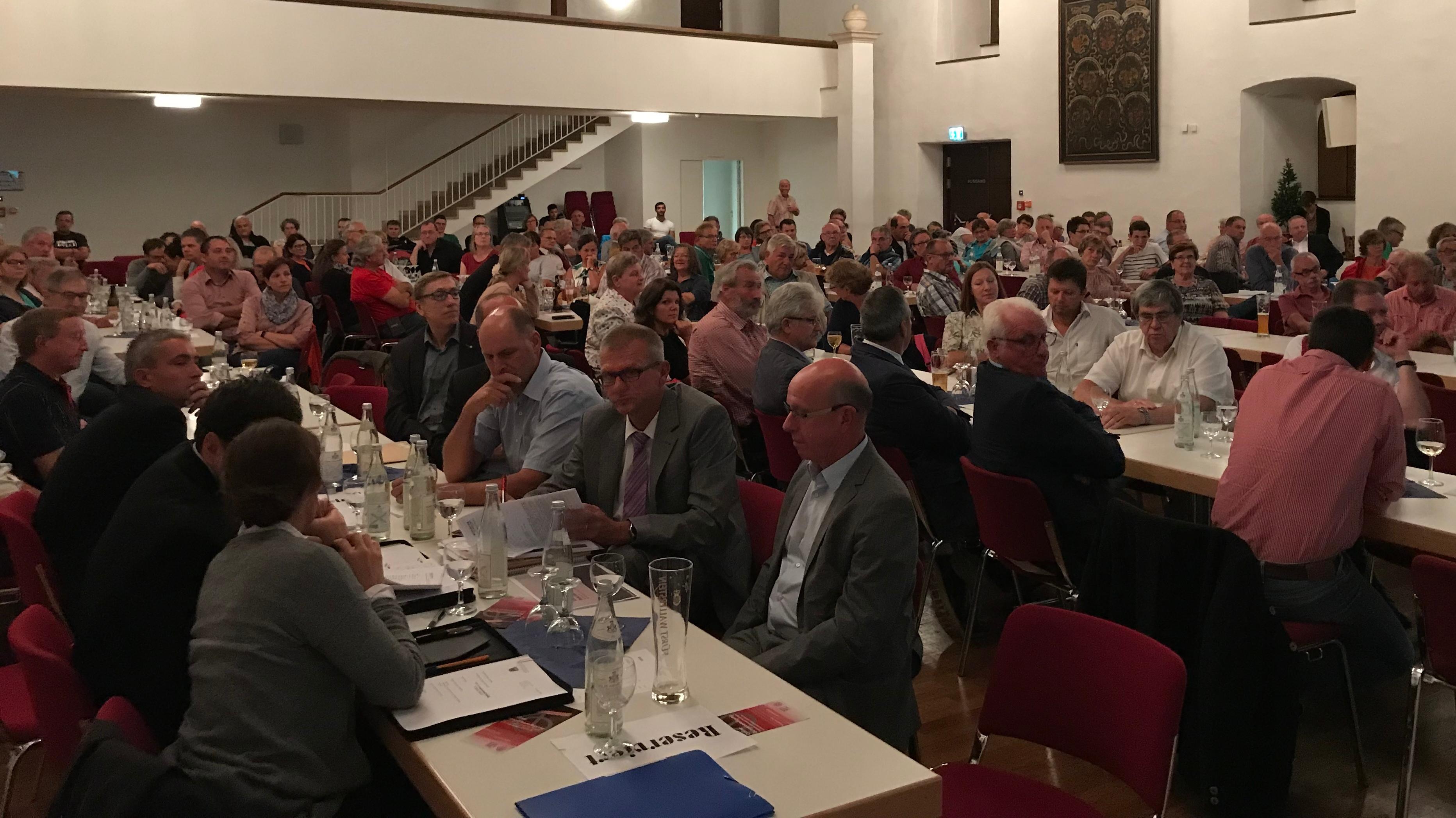 Zahlreiche Bürger sitzen bei einer Bürgerversammlung in Nördlingen an langen Tischen
