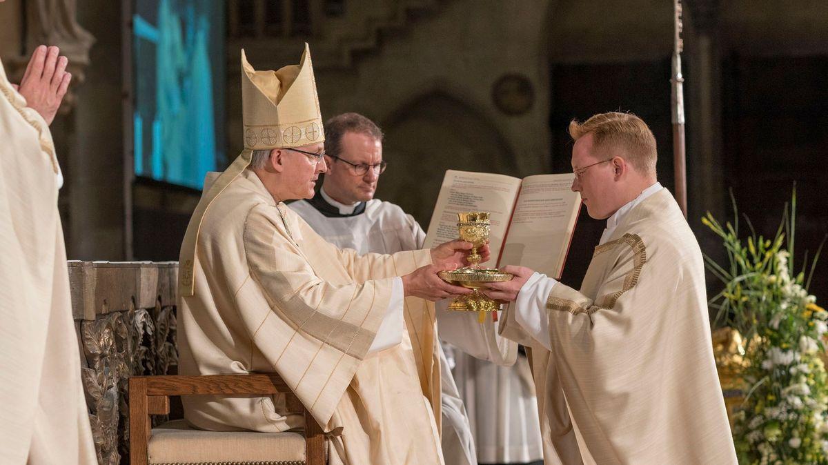 Bischof Rudolf Voderholzer überreicht Hostie und Kelch dem neuen Priester Dirk-Henning Egger
