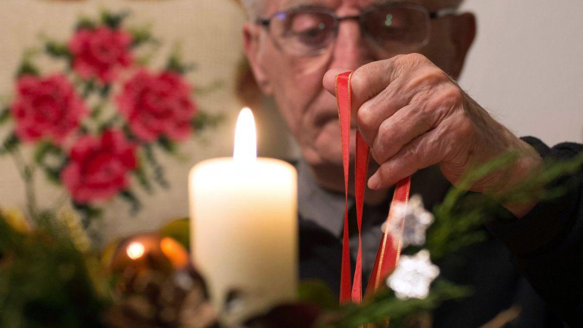 Mann sitzt alleine vor einer Kerze
