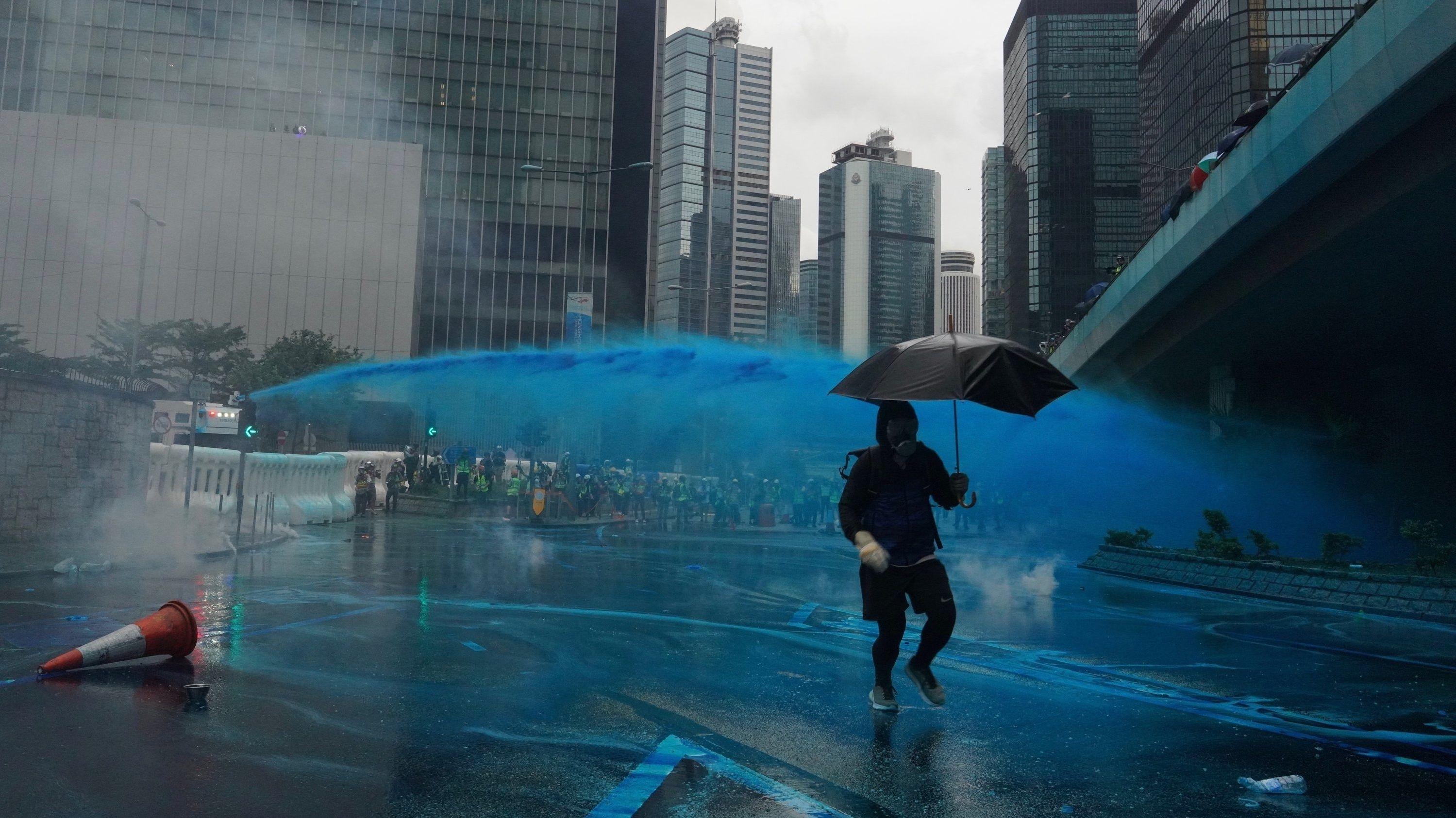 EinDemonstrant bringt sich vor dem blau gefärbten Wasserstrahl eines Wasserwerfers in Sicherheit.