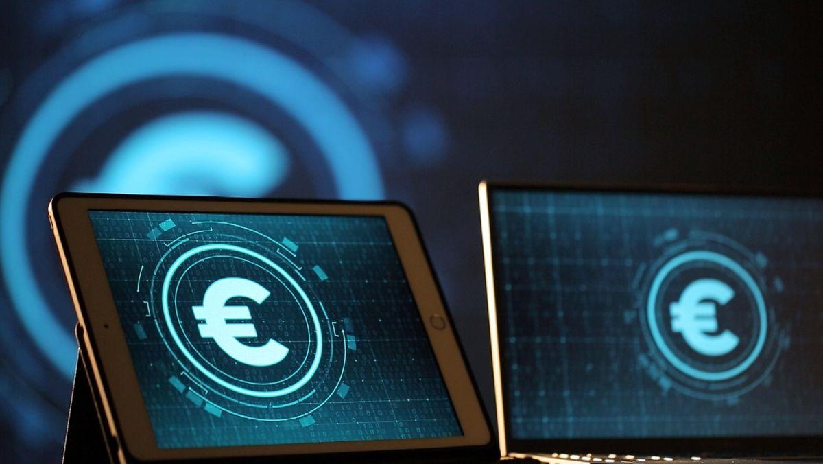 Ein Laptop und ein Tablet-PC, auf denen ein stilisierter digitaler Euro abgebildet ist