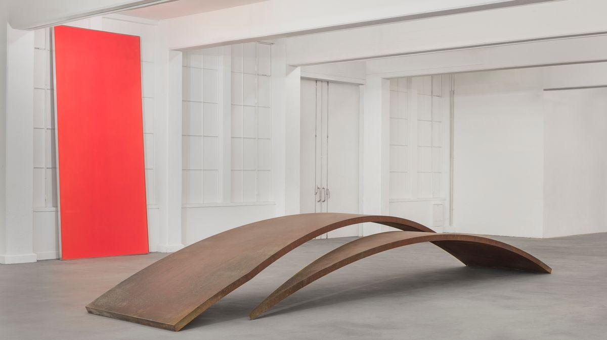 Großes hochformatiges leuchtend rotes Gemälde an der Wand eines Ausstellungsraums.  Im Vordergrund zwei wellenförmig gebotene Stahlskulpturen, die nur ganz eben den Boden zu berühren schienen.