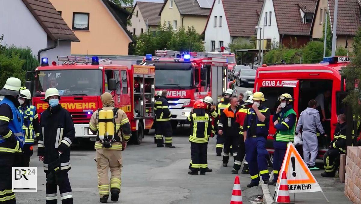 Viele Feuerwehrleute und Fahrzeuge stehen auf einer Straße in Grub am Forst.