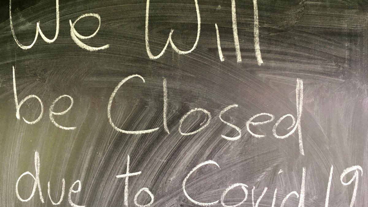 Eine Tafel, auf der mit Hand geschrieben ist, dass das Geschäft wegen Covid 19 aufgegeben wurde.