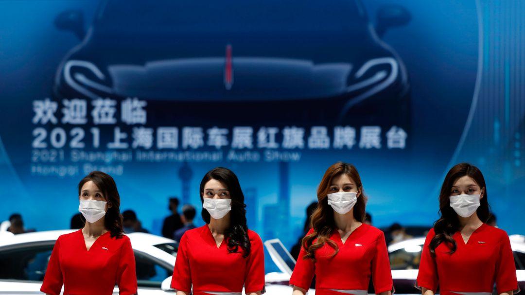 Vier chinesische Hostessen auf der Automesse in Shanghai Anfang 2021. Sie tragen rote Blusen und einen weißen Mundschutz.