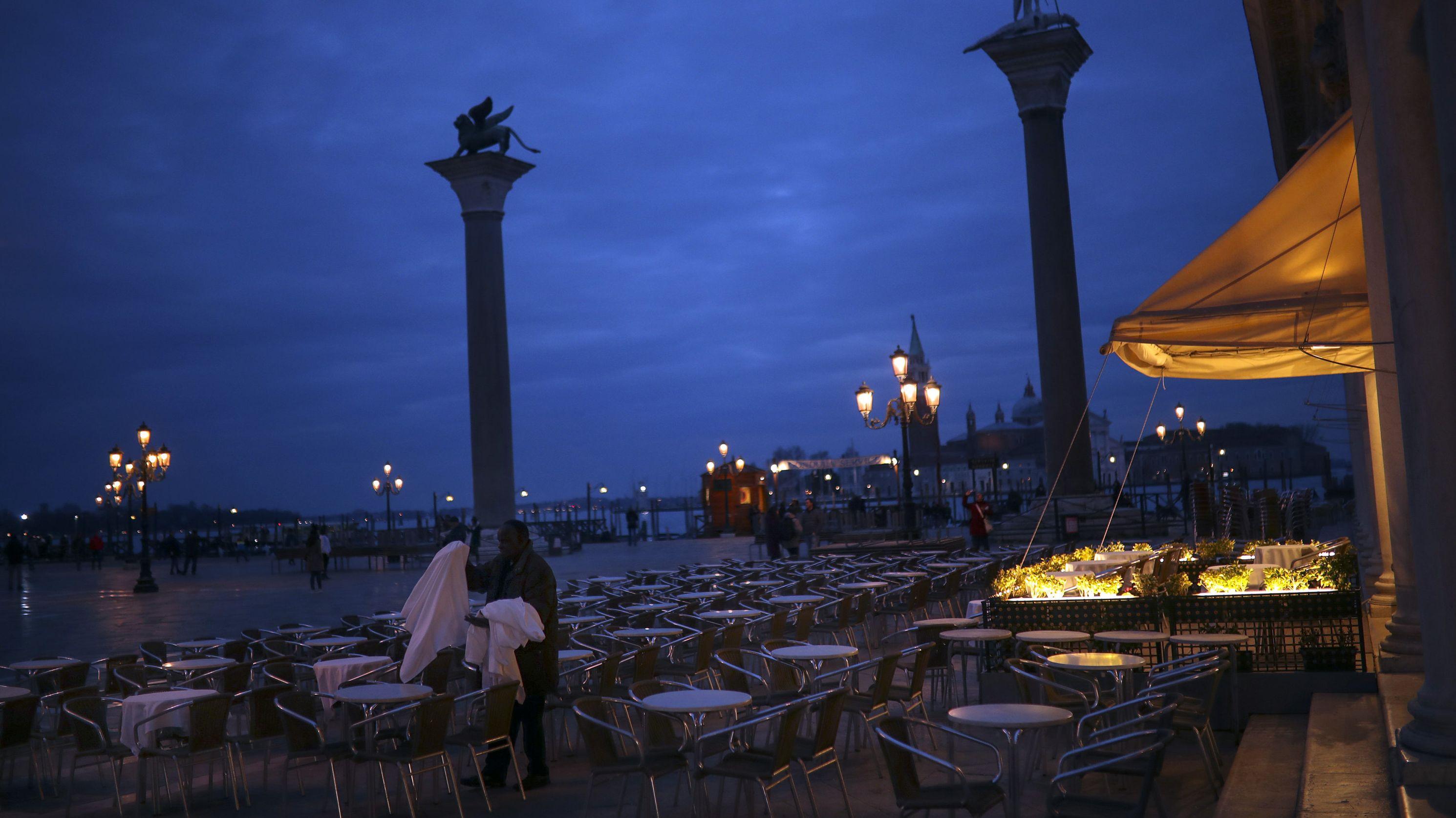 Leeres Straßencafe in Venedig in der Abenddämmerung - ein Mann holt die Tischdecken rein