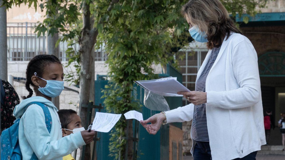 Auf dem Bild sieht man zwei Kinder, die von einer Lehrerin Zettel mit Informationen bekommen. Alle tragen einen Mund-Nasen-Schutz.